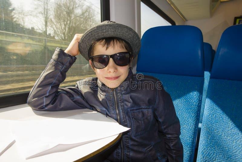 Il ragazzo bello in occhiali da sole guida su un treno immagini stock