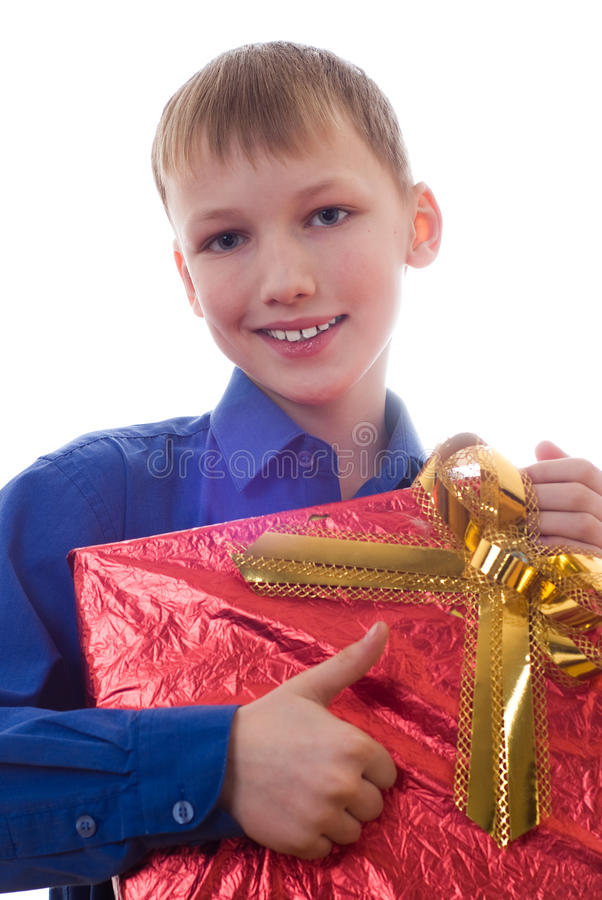 Il ragazzo bello in una camicia blu si leva in piedi con un regalo fotografia stock libera da diritti