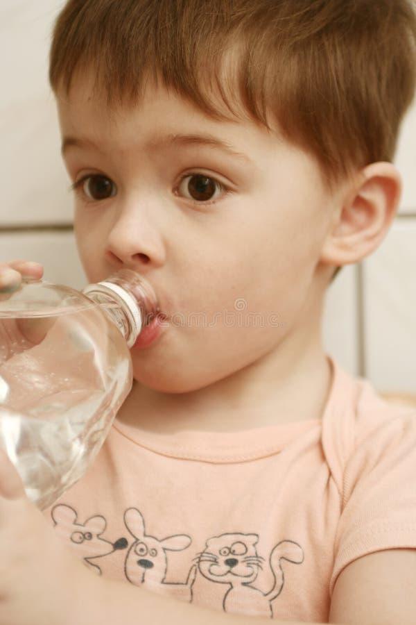 Il ragazzo beve l'acqua dalla BO fotografia stock libera da diritti