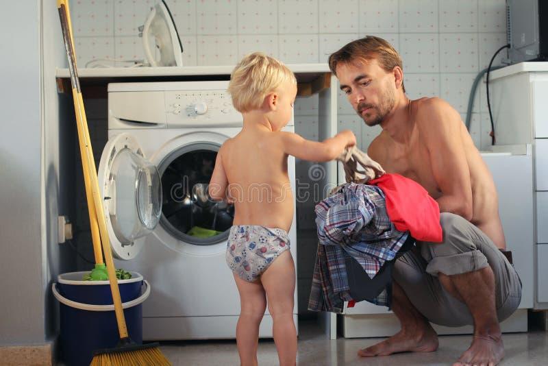 Il ragazzo biondo del bambino sveglio aiuta suo padre a mettere la lavanderia nella lavatrice Lavoro domestico della famiglia, co fotografia stock