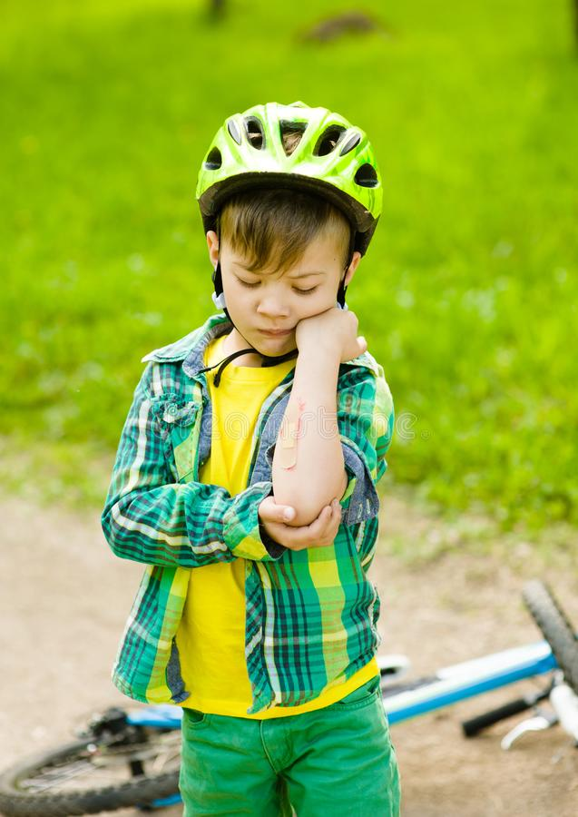 Il ragazzo ? caduto dalla bici in un parco immagine stock libera da diritti