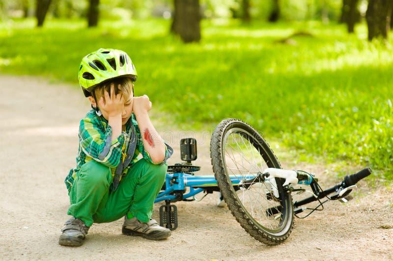 Il ragazzo ? caduto dalla bici in un parco fotografie stock libere da diritti