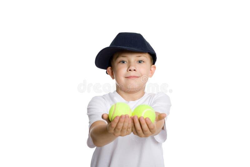 Il ragazzo cattura le sfere di tennis immagine stock