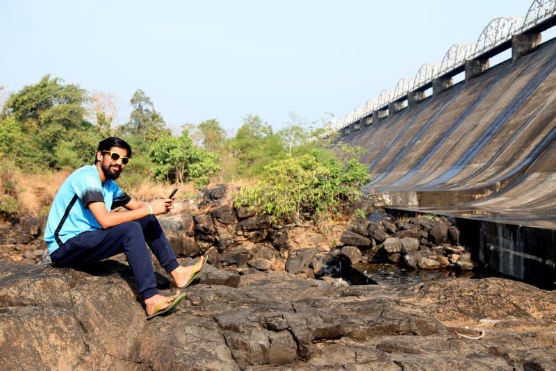 Il ragazzo che guarda una diga si siede vicino ad un fiume in maharashtra India fotografia stock libera da diritti