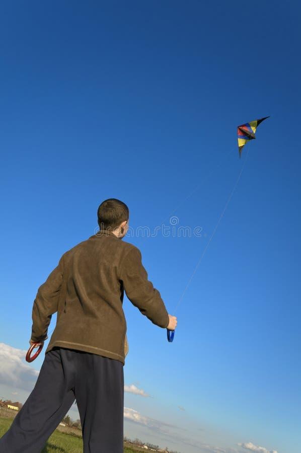 Il ragazzo che pilota un aquilone indietro si inclina immagine stock