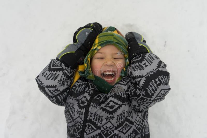 Il ragazzo che ride come neve cade sul fronte fotografie stock libere da diritti