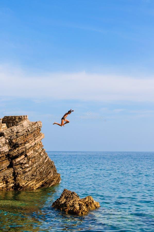 Il ragazzo che salta fuori dalla scogliera nell'acqua blu fotografia stock libera da diritti