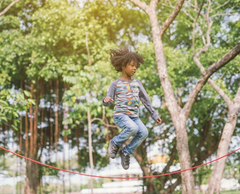 Il ragazzo che salta sopra la corda nel parco il giorno di estate soleggiato fotografia stock