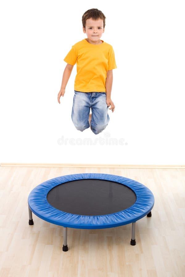 Il ragazzo che salta su sul trampolino immagine stock libera da diritti