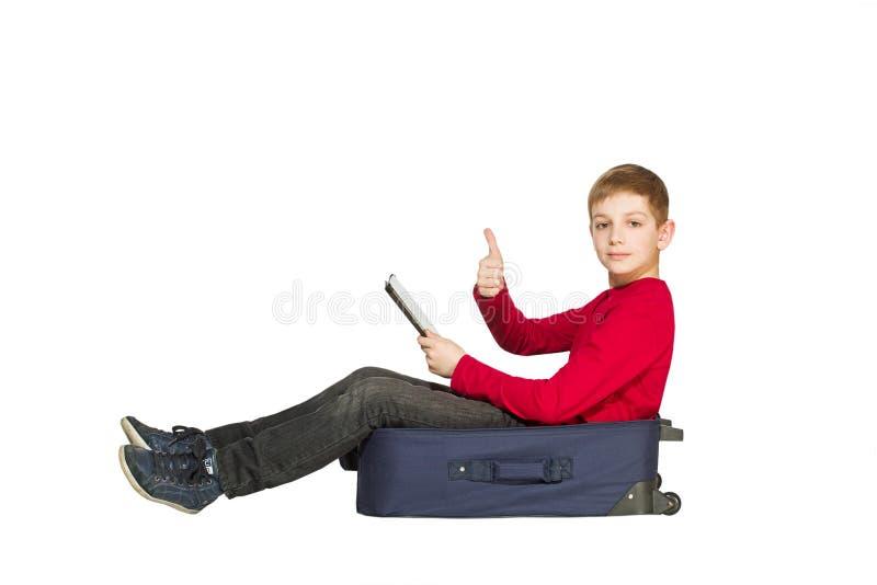 Il ragazzo che si siede sul viaggio insacca la compressa della tenuta che calza il pollice su immagine stock