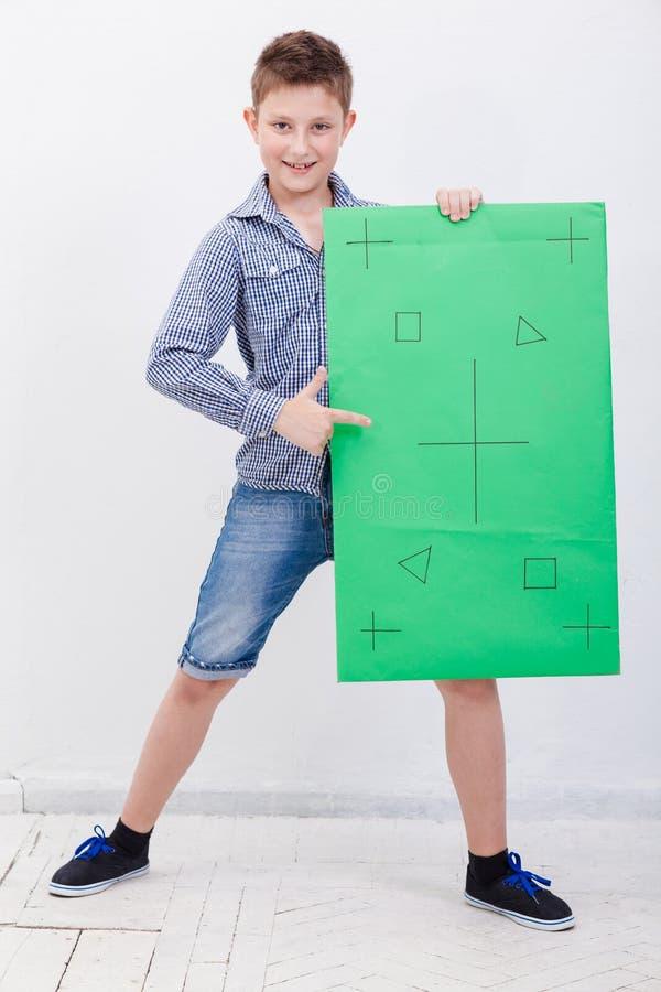 Il ragazzo che tiene un'insegna su fondo bianco fotografia stock libera da diritti