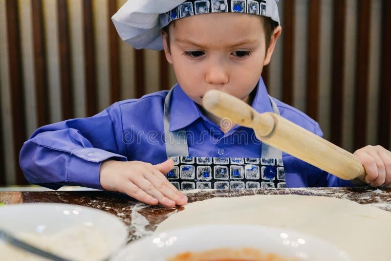 Il ragazzo con il cappello del cuoco unico che prepara la pizza italiana in pizzeria esclude il ristorante fotografia stock