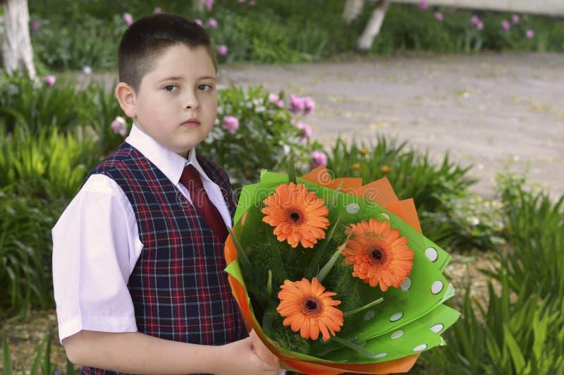 Il ragazzo con i fiori va a scuola, l'ultima chiamata fotografia stock libera da diritti