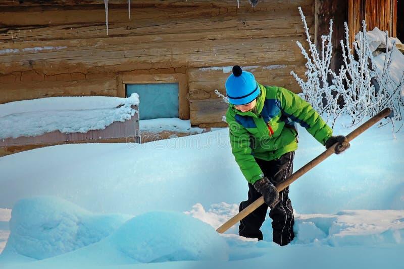 Il ragazzo con una pala rimuove il percorso dopo le precipitazioni nevose Lavoro infantile nella vita rurale fotografie stock