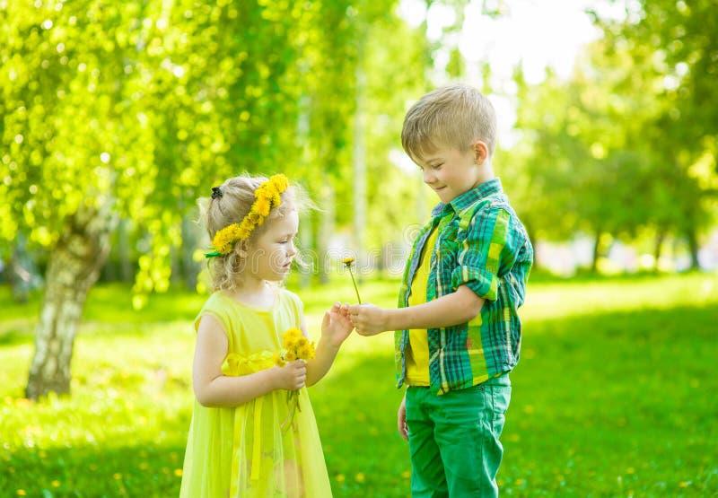 Il ragazzo d? una ragazza di fiore nel giorno di estate del parco immagine stock libera da diritti