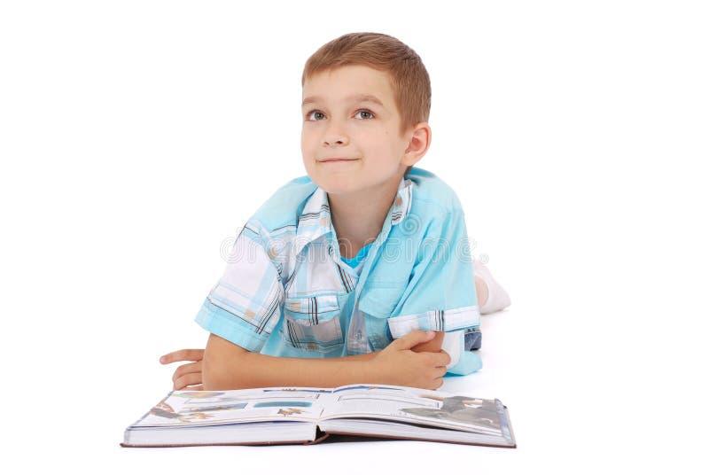 Il ragazzo dei giovani sogna vicino al libro aperto immagine stock libera da diritti
