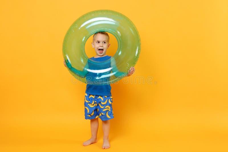 Il ragazzo del bambino 3-4 anni in vestiti blu dell'estate della spiaggia giudica l'anello gonfiabile isolato sul fondo giallo ar fotografia stock