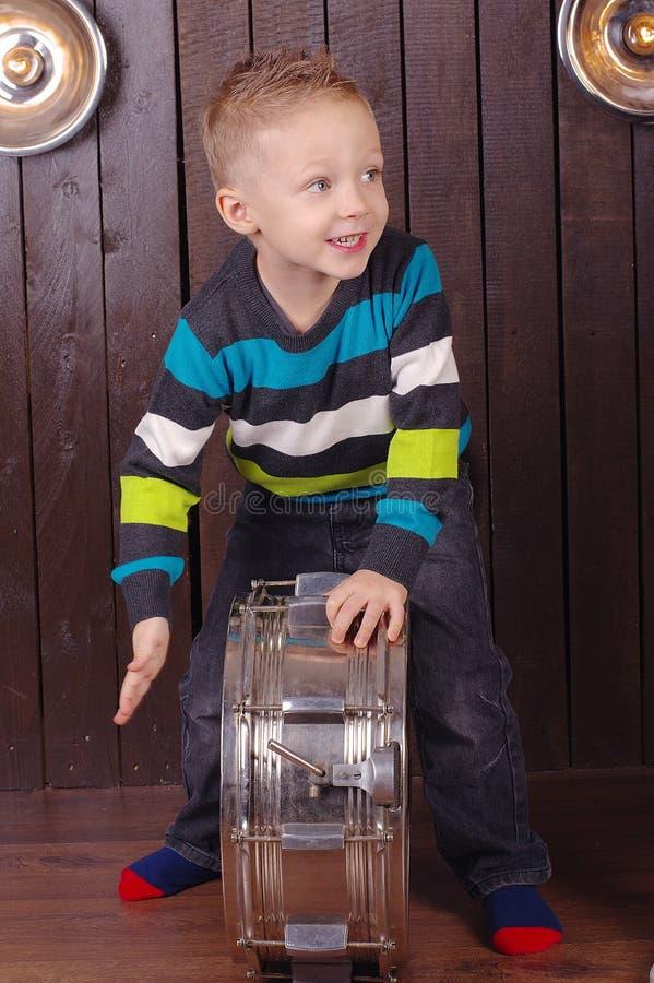 Il ragazzo del bambino gioca il tamburo Priorità bassa di legno immagine stock libera da diritti