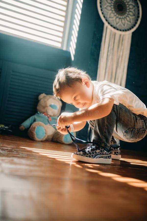 Il ragazzo del bambino impara legare i laccetti sulle sue scarpe da tennis fotografia stock libera da diritti
