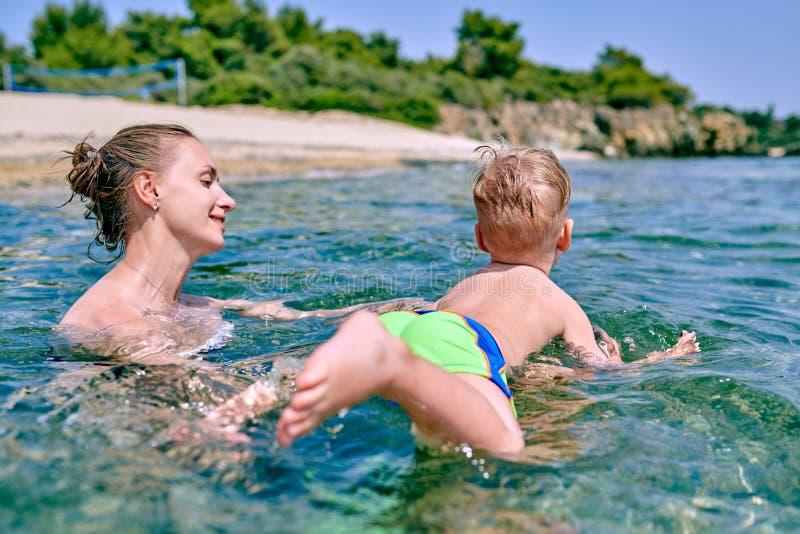 Il ragazzo del bambino impara nuotare con la madre fotografia stock libera da diritti