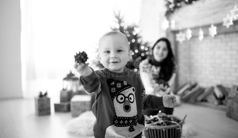 Il ragazzo del bambino sta giocando contro lo sfondo dell'albero di Natale immagini stock
