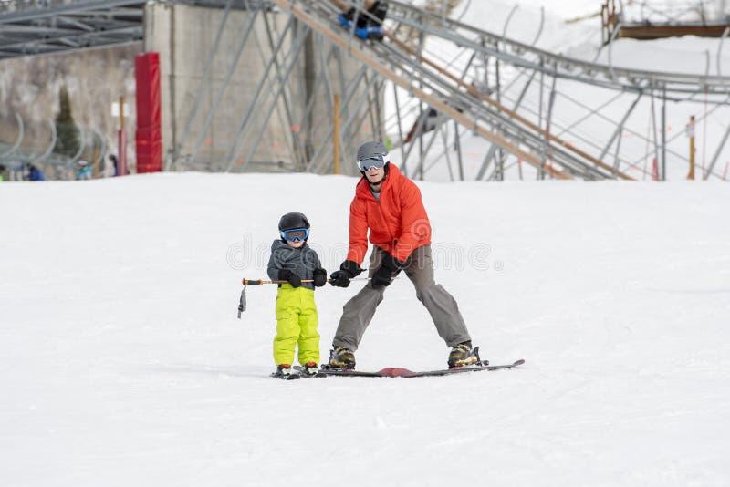 Il ragazzo del bambino vestito calorosamente & in buon ingranaggio della sicurezza impara sciare con il suo papà fotografia stock libera da diritti