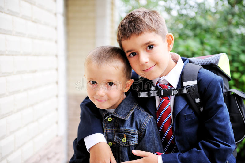 Il ragazzo del First-grader abbraccia il suo fratello minore fotografia stock libera da diritti