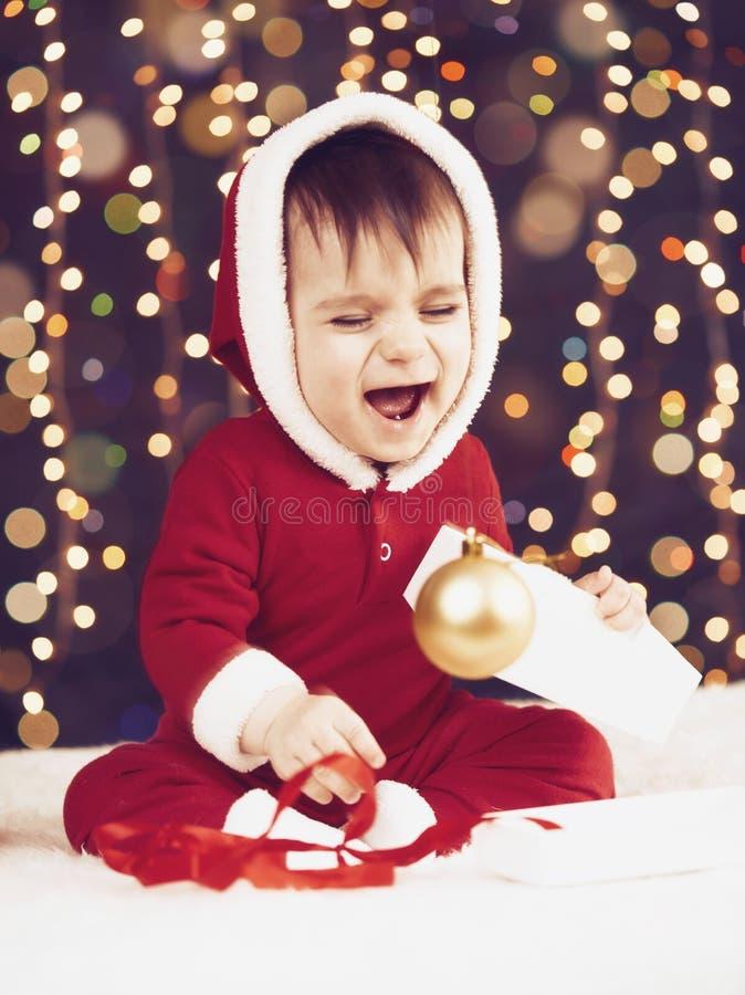 Il ragazzo del piccolo bambino vestito come Santa che gioca con la decorazione di natale, il fondo scuro con l'illuminazione e il fotografia stock