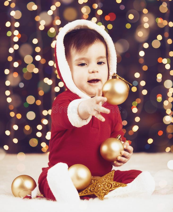 Il ragazzo del piccolo bambino vestito come Santa che gioca con la decorazione di natale, il fondo scuro con l'illuminazione e il fotografia stock libera da diritti