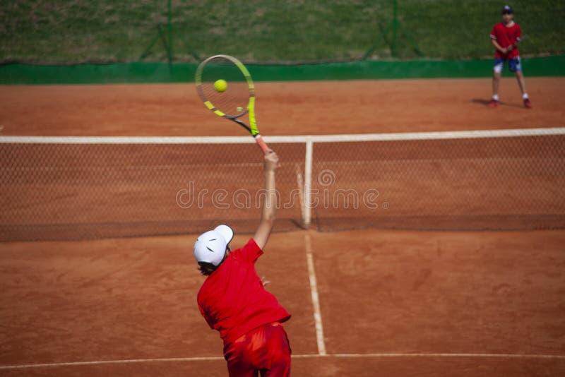 Il ragazzo del tennis che serve dentro sceglie il torneo di tennis fotografie stock