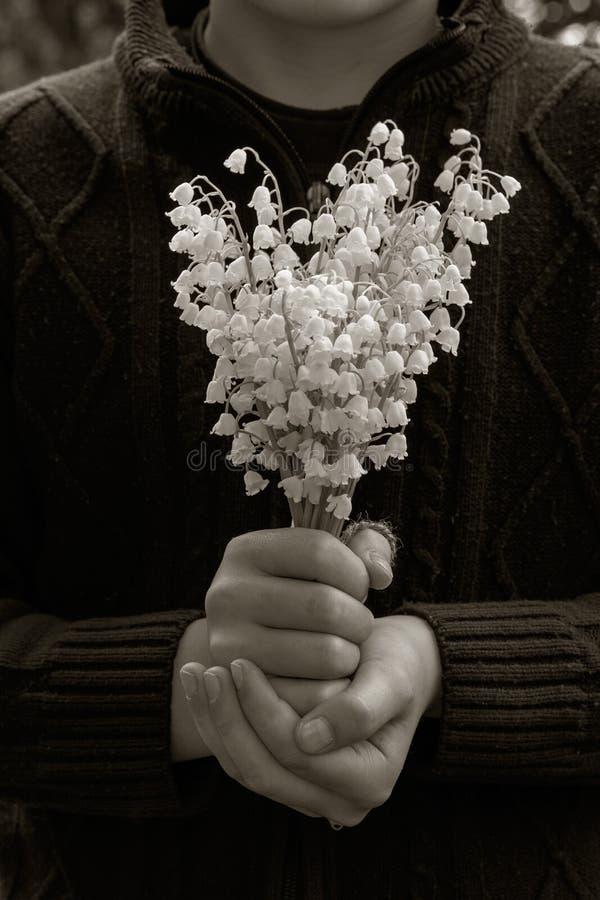 Il ragazzo del villaggio dentro tricotta il maglione con un mazzo dei fiori bianchi dei mughetti in sue mani fotografia stock