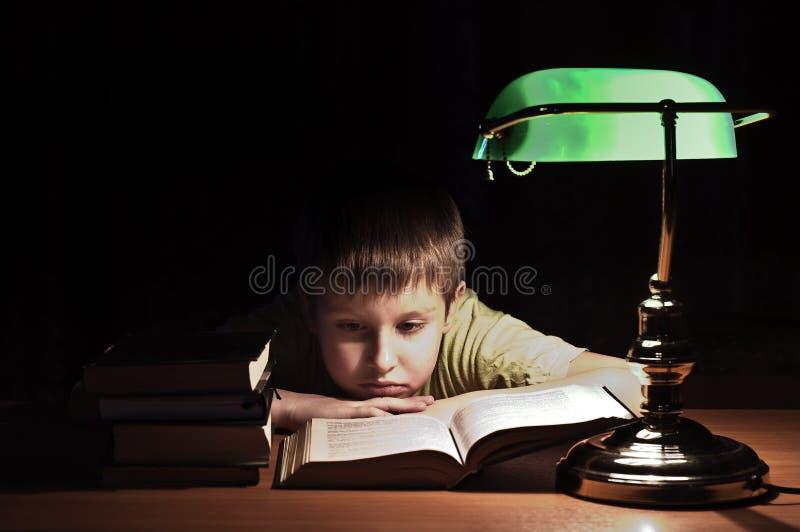 Il ragazzo delle biblioteche legge il libro immagine stock
