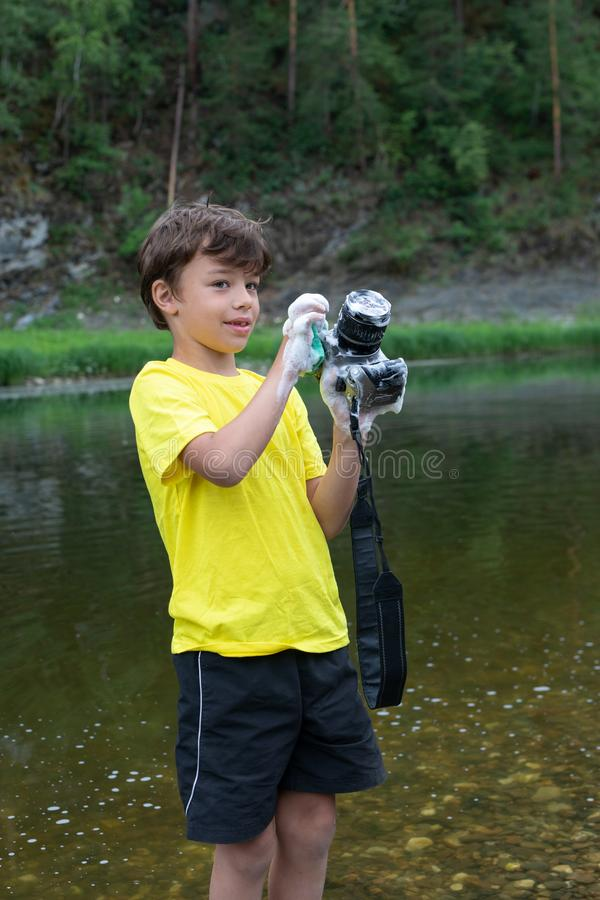 Il ragazzo di 9 anni lava una macchina fotografica male pulire la macchina fotografica e la lente immagini stock