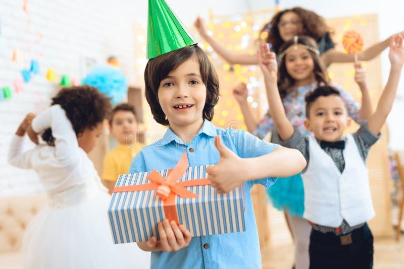 Il ragazzo di buon compleanno in cappello festivo verde indica che è soddisfatto del regalo fotografia stock