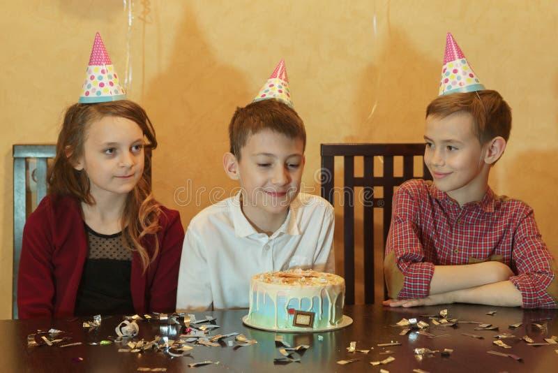 Il ragazzo di compleanno ed i suoi amici per la tavola di festa torta di compleanno al partito del ` s dei bambini fotografia stock libera da diritti