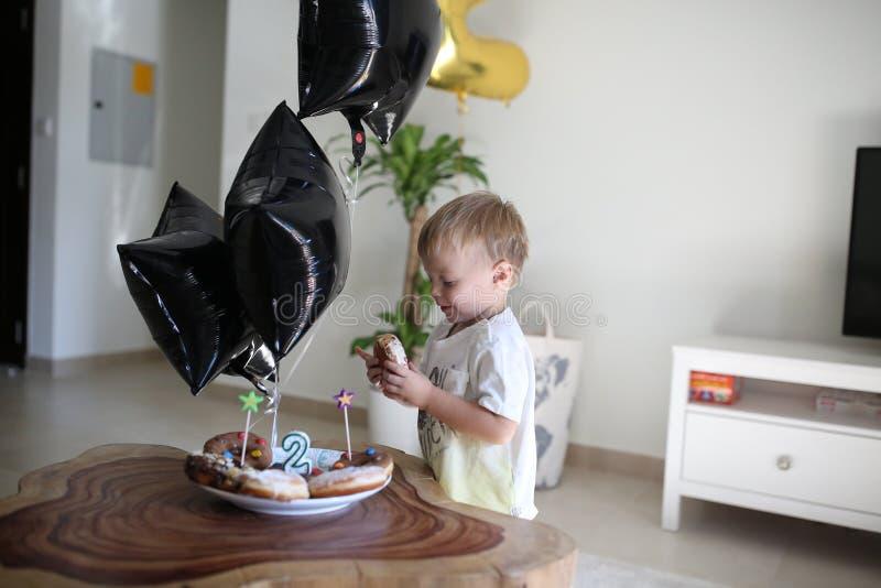 Il ragazzo di compleanno sta esaminando le sue guarnizioni di gomma piuma di compleanno immagini stock libere da diritti
