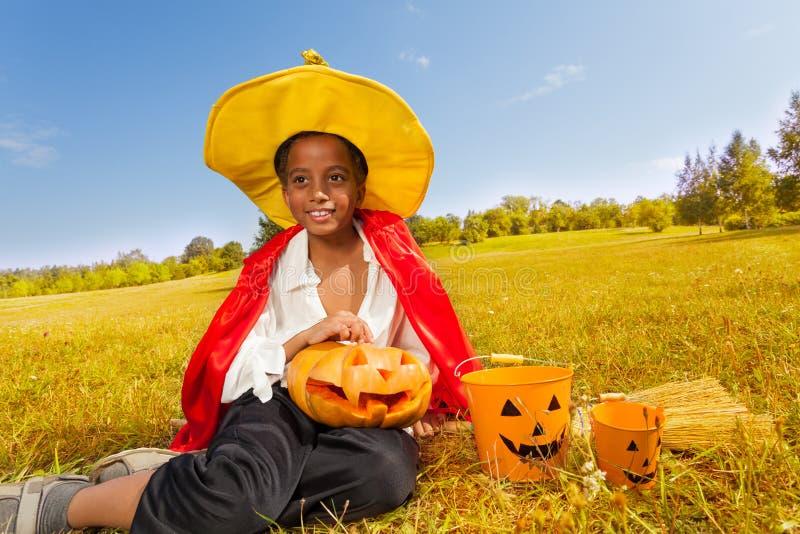 Il ragazzo di Halloween si siede su erba gialla con la zucca fotografie stock libere da diritti