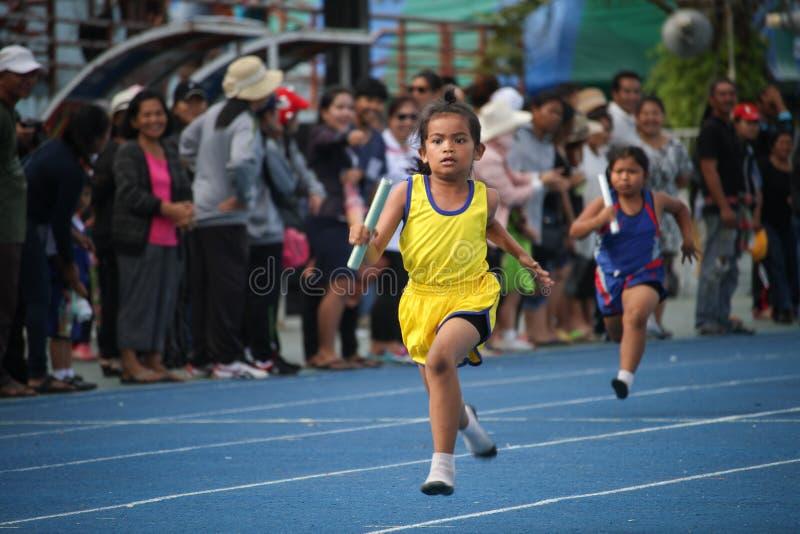Il ragazzo di scuola sta dirigendosi durante la corsa di relè del festival del giorno di sport fotografia stock libera da diritti