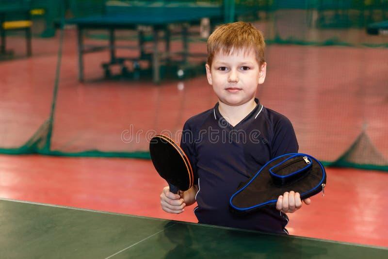 Il ragazzo di sette anni negli sport forma la tenuta un argomento e della racchetta per ping-pong immagine stock