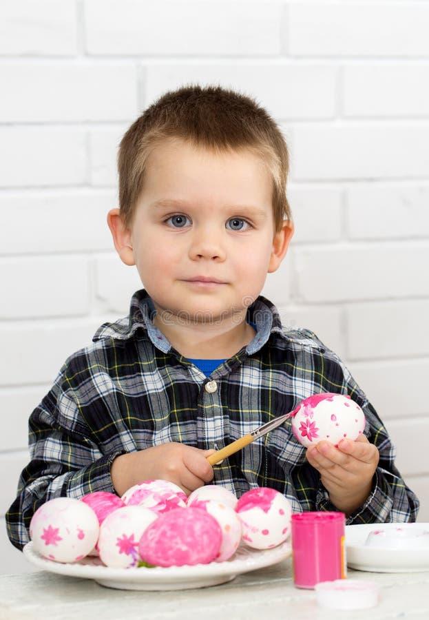 Il ragazzo dipinge le uova fotografie stock libere da diritti