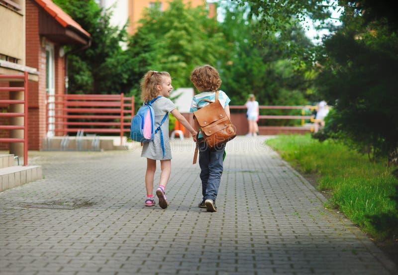 Il ragazzo e il gerlie vanno a scuola prender per manosi immagini stock