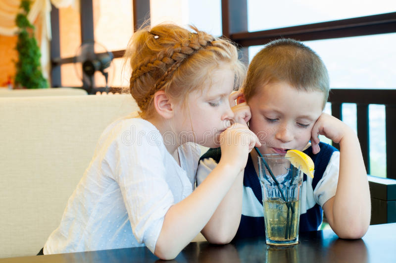 Il ragazzo e la ragazza bevono una bevanda immagini stock