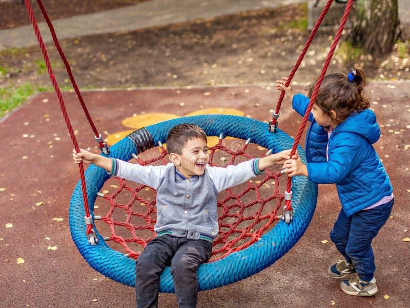 Il ragazzo e la ragazza felici hanno un'oscillazione sul campo da giuoco fotografie stock