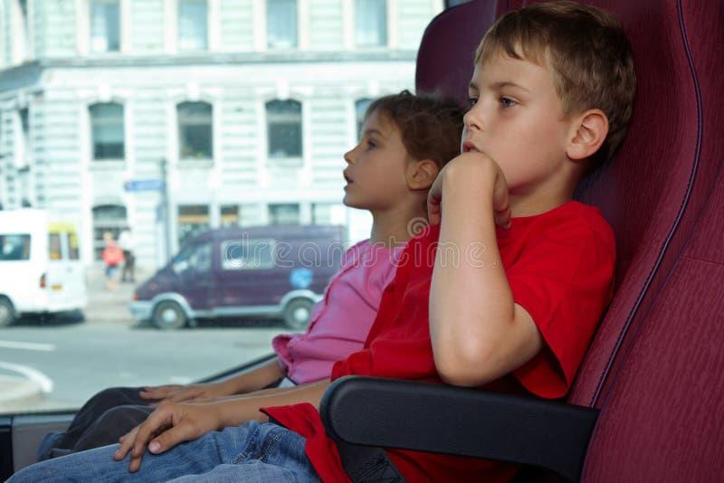 Il ragazzo e la ragazza si siedono in presidenze in bus fotografia stock libera da diritti