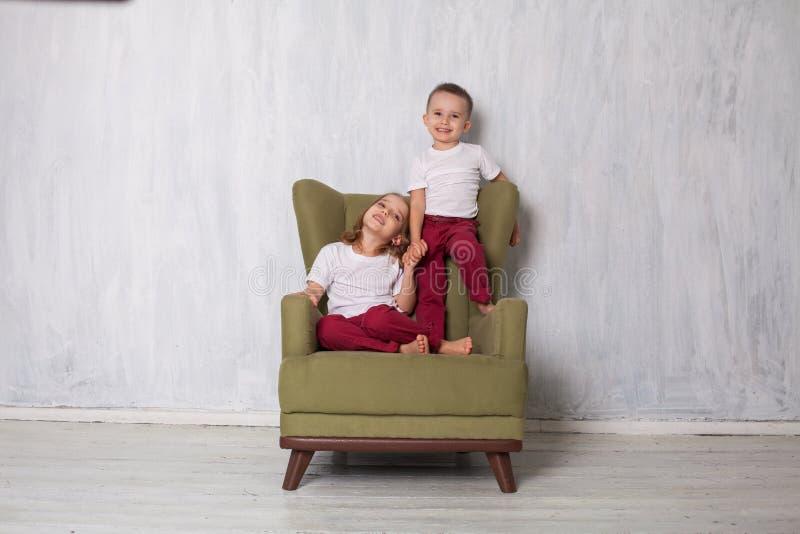 Il ragazzo e la ragazza sono il fratello e la sorella si siede su uno strato verde nella stanza fotografia stock