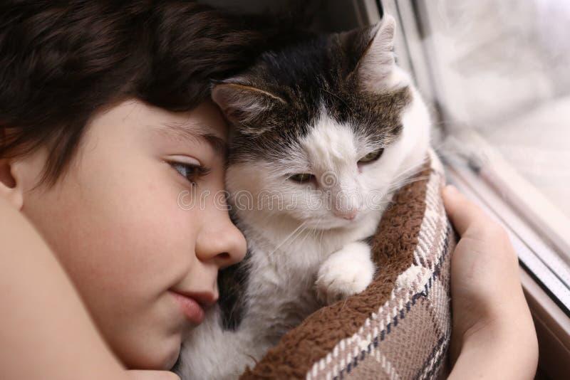 Il ragazzo ed il gatto dell'adolescente in gatto accogliente inseriscono il nido che dorme nel fine settimana mattina fotografia stock