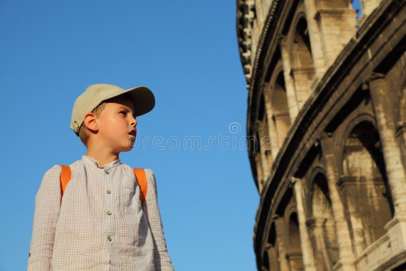 Il ragazzo esamina le pareti del Colosseo immagini stock