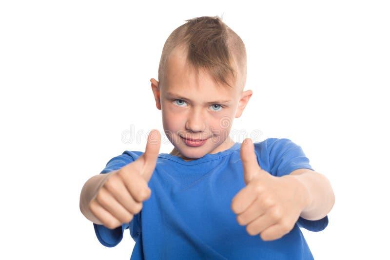 Il ragazzo felice che mostra i pollici aumenta il gesto fotografie stock