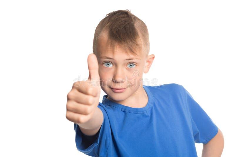 Il ragazzo felice che mostra i pollici aumenta il gesto fotografia stock