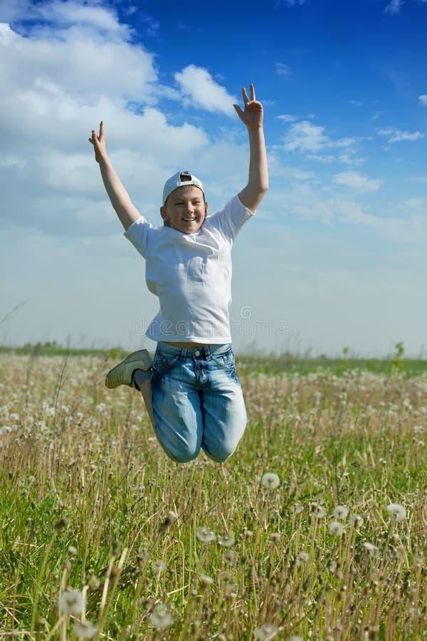 Il ragazzo felice dell'adolescente salta al prato fotografie stock
